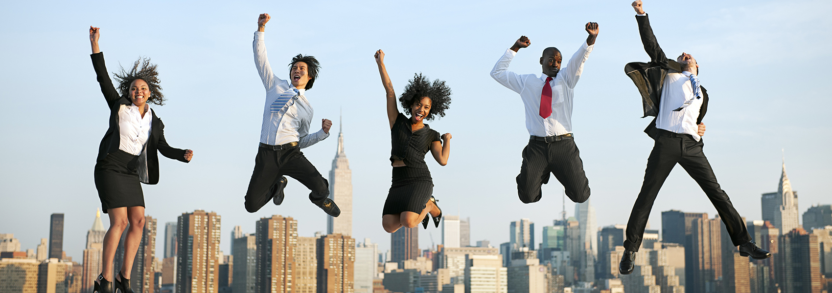 5 professionals jumping up in the air with joy