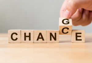 "Hand flips wooden cubes to change the word ""change"" to ""chance"""