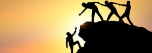 figures reaching out to help a man climbing up a mountain
